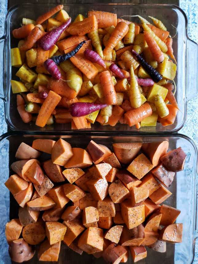 Two glass baking dishes, seen from above. One is full of cut chunks of orange sweet potato. The other is full of chopped and whole rainbow carrots. They're still raw, ready to go into the oven to roast. You can see shiny coat of oil, salt, and pepper across them.