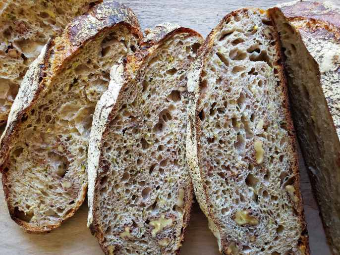 An image of 3 slices of sourdough bread displayed showing their insides. To the right of the slices there is the rest of the loaf of bread. There is a nice and brown crusty crumb showing on both sides of the bread and it is also littered with air holes, walnuts, and specks of zucchini.