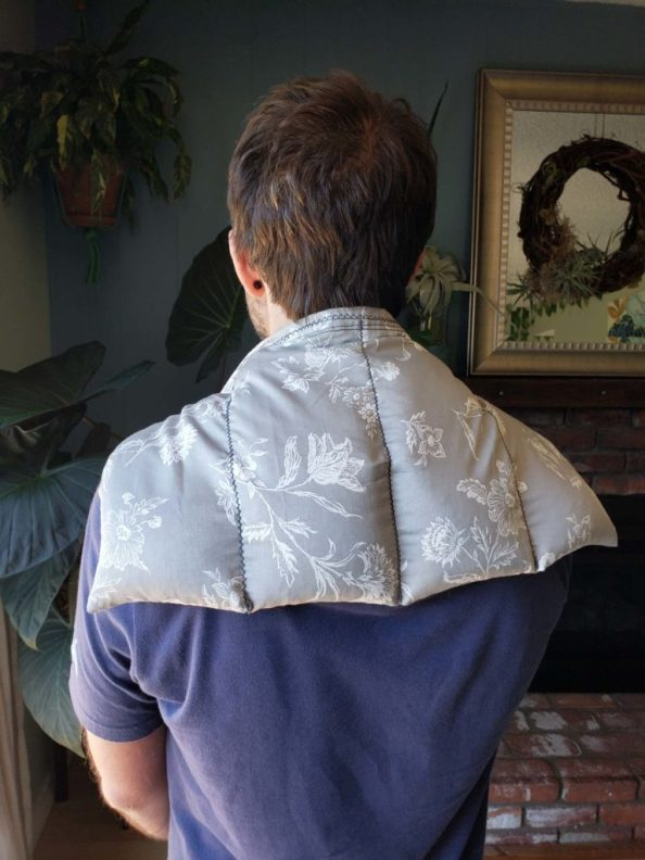 """A man is standing with his back to the camera, the rice heat pad which was made from a grey pillowcase with floral patterns in white has be laid over his shoulders as one would a cape. There is a brick fireplace in the background with a large alocasia or """"elephant ear"""" in the corner with a hanging plant above it. There are miscellaneous tillandsias on the mantle."""