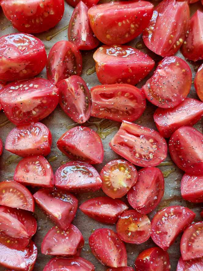 A closeup image of the halved and quartered red tomatoes after they have been drizzled with olive oil and sprinkled with sea salt and black pepper. They are now ready to go into the oven.