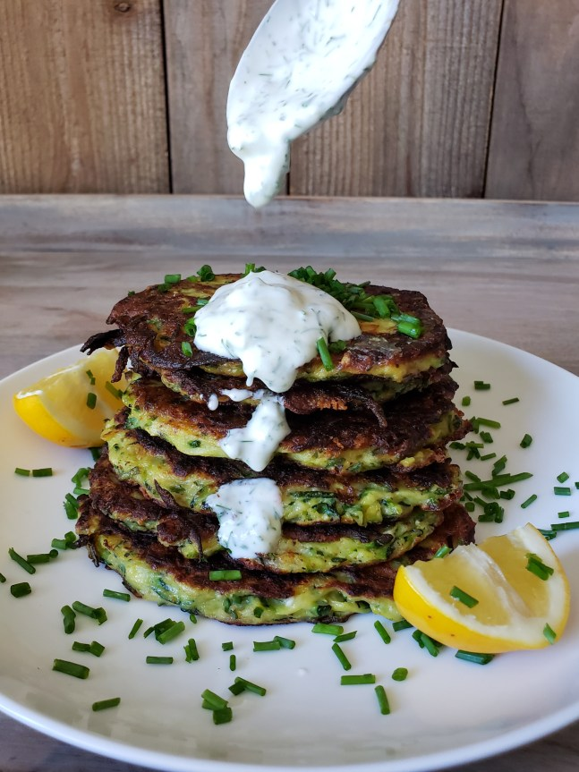 Six cooked zucchini fritters are stacked one atop one another like a stack of pancakes. They are golden grown and the edges reveal a golden yellow quiche like look. The plate has been garnished with chopped chives and two wedges of lemon. A spoon is dropping in from the top of the image dropping a dollop of yogurt dill sauce on the stack. It has landed on the top fritter and has partially slid off the front side of the stack, getting sauce on the remaining fritters below.