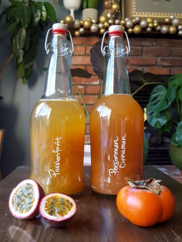 Passionfruit and Persimmon Cinnamon flavored fermented tea sit atop a dark wood table. They are both a wonderful dark golden yellow in color, with the persimmon flavor displaying a slightly more dark color. Their raw fruit ingredients flank each bottle with a passionfruit cut in half on one side and a whole persimmon on the other.