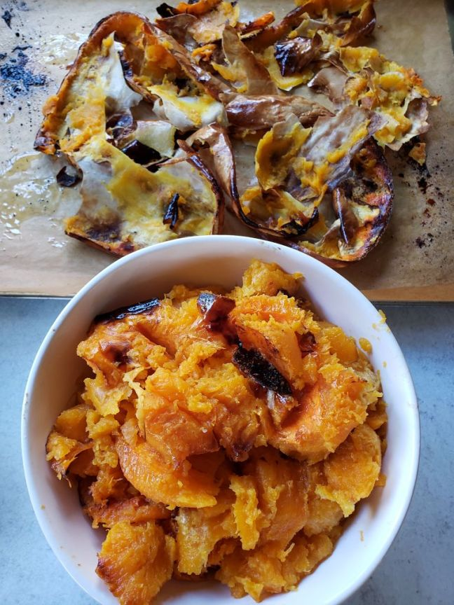 The butternut squash is shown after it has been scooped out of its skin after roasting. The roasted butternut squash flesh is sitting in a white ceramic bowl, while the detached skin portion of the squash sits alone above it.