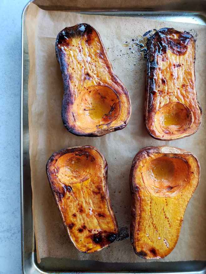 The butternut squash have both been cut in half lengthwise, the seed portion was scooped out, and they lay on a baking sheet after being roasted. The flesh has caramelized and turned black to dark brown in some spots due to the roasting process. It is now ready to be added to the soup once it cools.