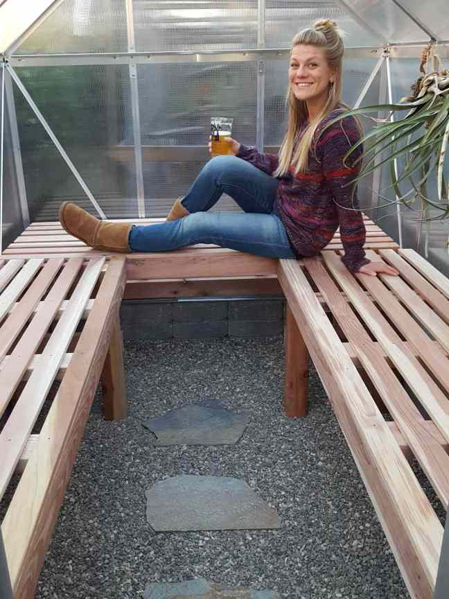 DeannaCat inside her finished greenhouse, she is sitting on her newly constructed slatted wood potting benches, she is enjoying a cold, carbonated beverage in victory of the newly constructed additions. The smaller pea gravel flooring is visible along with a few flagstone pavers down the middle of the pathway.