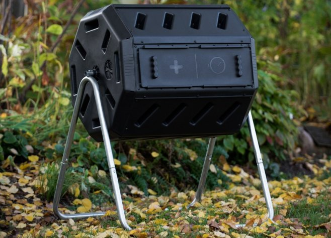 A black plastic compost tumbler sits amongst a wooded area. The tumbler contains two compartments so you can feed on side while letting the other side break down further.