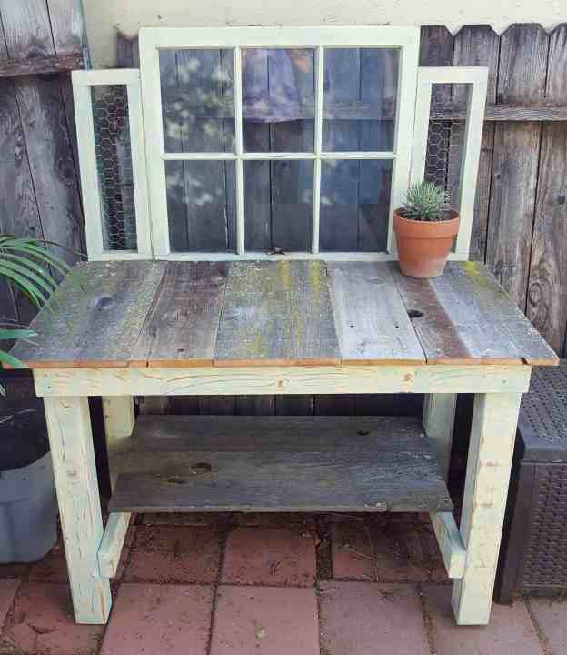A handmade potting bench is shown, it has a bottom shelf and the main top work surface. An old window has been connected to the back of the bench for decoration while keeping things from falling off the backside of the bench. Old barn wood has been used for the table and shelf surface while it has been framed out with 2x4 and 4x4 boards which have been painted and sanded to make a worn or vintage look. A potting bench would be a useful gift for any gardener.