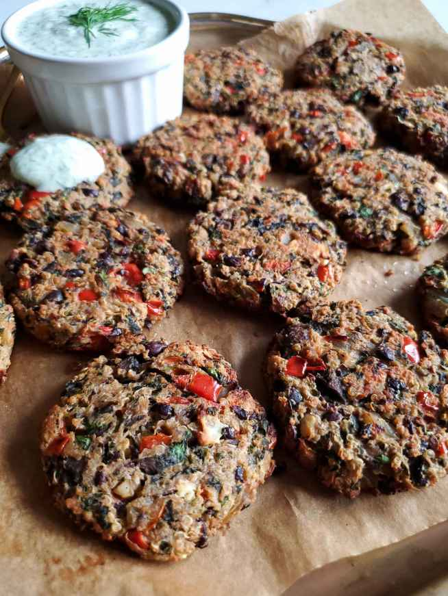 Black bean and quinoa veggie burgers displayed on a platter lined with parchment paper. A white ramekin is nestled amongst the burgers full of yogurt dill dipping sauce. The burgers are golden brown and have specks of red bell peppers, black beans, and cilantro.