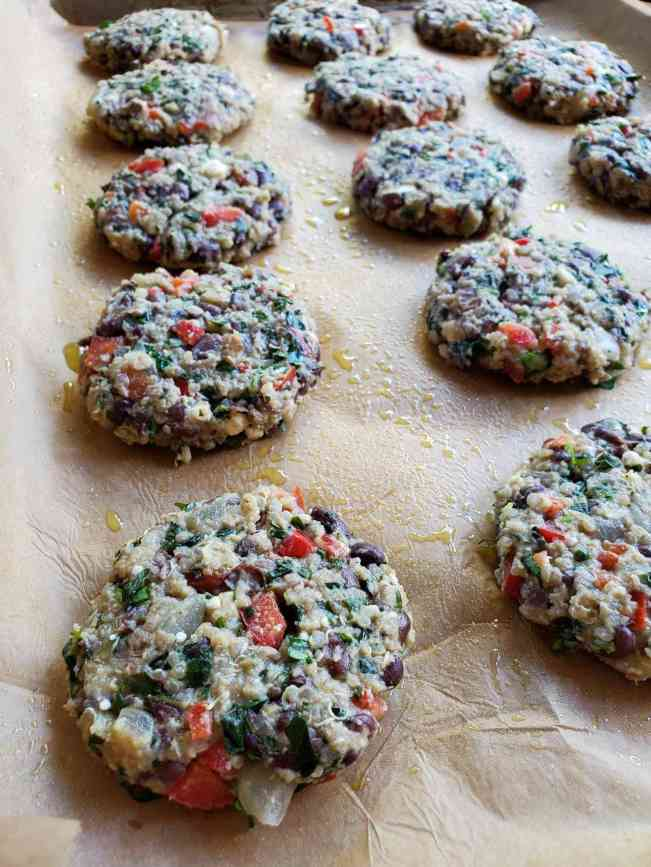 A parchment paper lined baking sheet filled with 3 inch round black bean and quinoa patties neatly lined up in rows. There are droplets of oil visible on the parchment paper which will keep the patties from sticking to the paper.