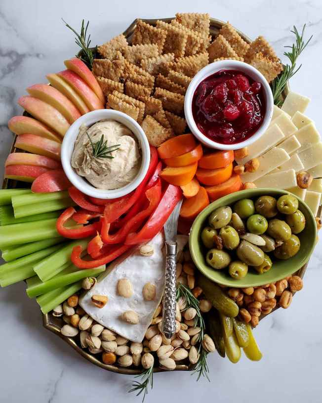 A cheese plate filled with sourdough crackers, cheddar, brie, slices of apple, persimmon, red bell pepper, celery, pistachios in their shell, slices of pickle, and corn nuts. There are three ramekins interspersed throughout the plate, one contains various green olives, another contains hummus, and the third contains fresh cranberry sauce. Sprigs of rosemary are sticking out of the plate here and there as a garnish.