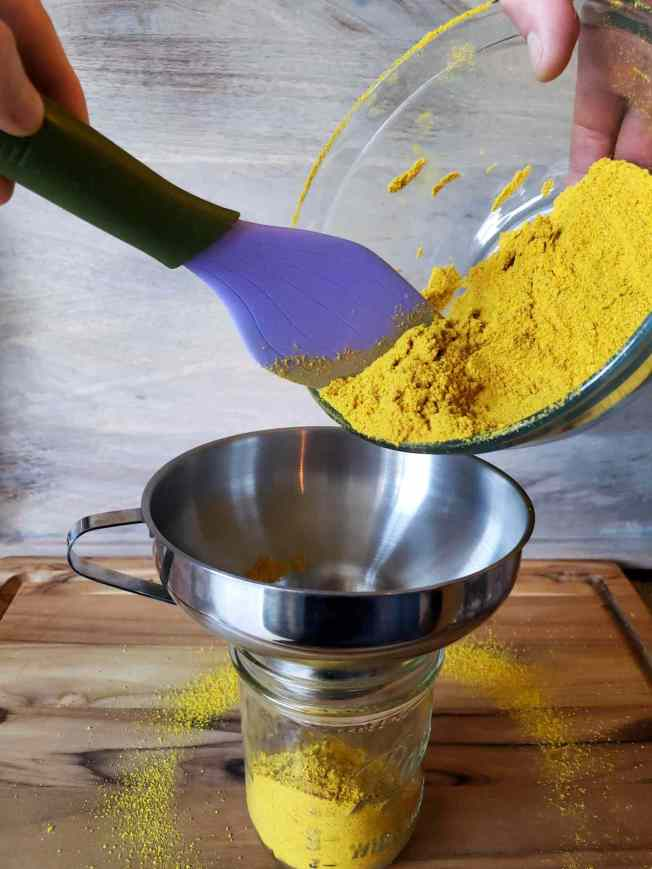 A glass bowl of turmeric powder is being poured into a glass pint mason jar for long term storage with a stainless steel canning funnel on top of it to control spillage. There is a light ring of turmeric powder surrounding the mason jar.
