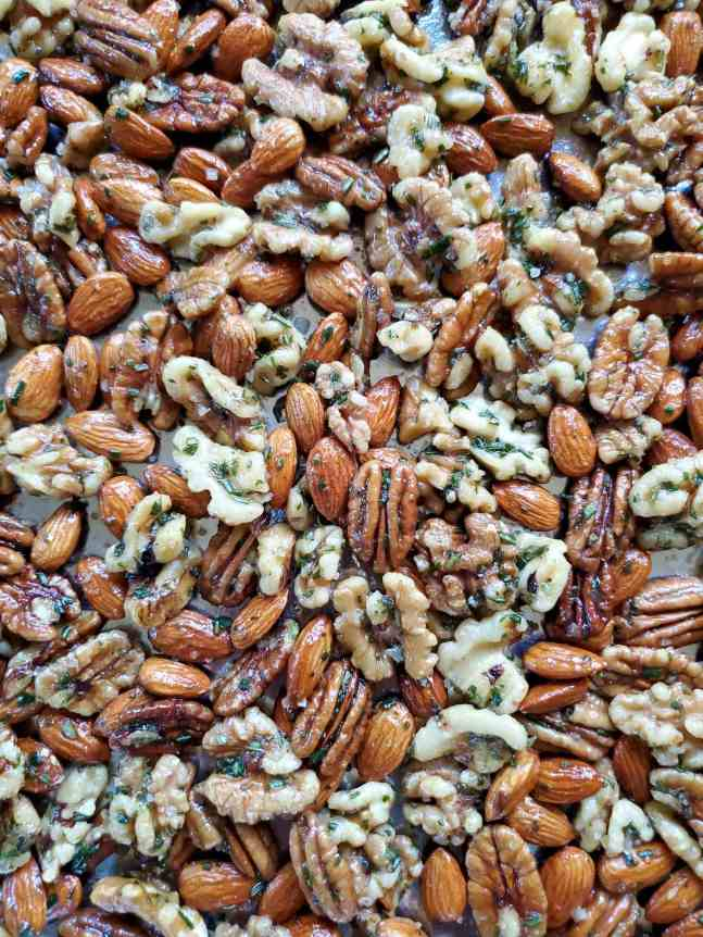Fresh almonds, walnuts, and pecans have been mixed with maple syrup, fresh chopped rosemary, and salt. They are scattered across a baking sheet, ready for the oven and soon to be sweet and salty rosemary roasted nuts.