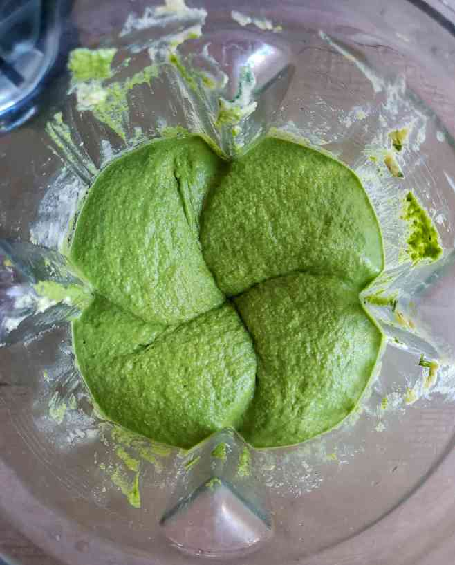 The green humus is shown in a blender after all of the ingredients have been added and blended together. The color is a vivid mint green with a smooth looking texture.