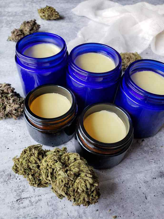 An image of three large blue glass jars and two smaller amber glass jars full of cannabis salve that contains CBD. there are numerous dried cannabis flowers arranged around the jar, ranging in color from golden green to purplish green. The salve is a light cream yellow in color.