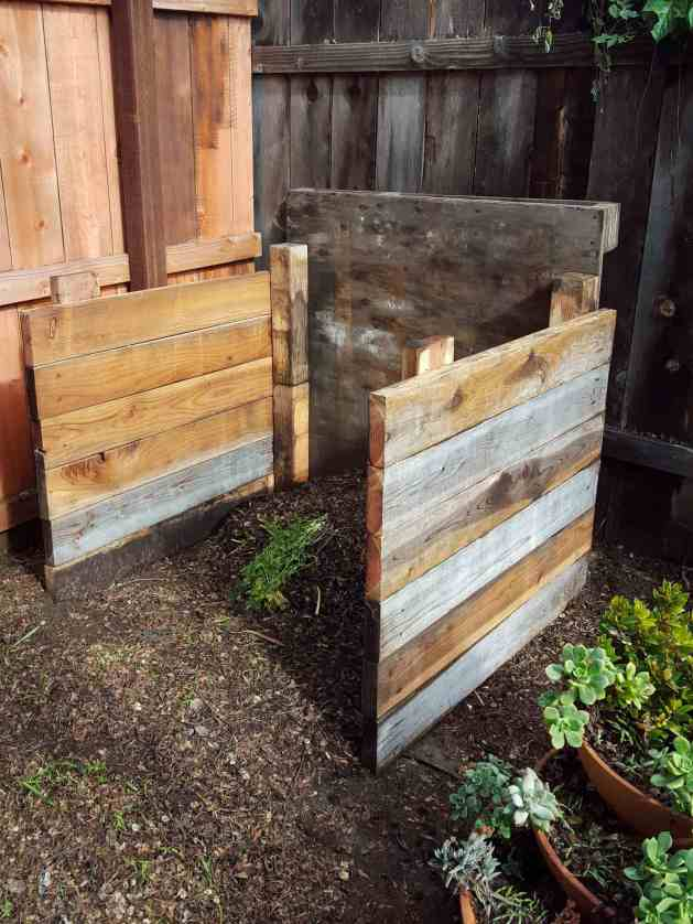 A three sided wooden single compartment compost bin is shown with a small amount of green and brown material in various stages of decomposition inside it. There is a three tiered pot nearby full of succulents.