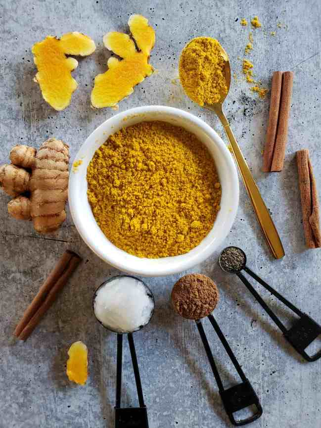 A white ceramic ramekin is centered in the image full of turmeric powder, there are cinnamon sticks, fresh turmeric pieces, spoons full of coconut oil, cinnamon, and black pepper scattered around the ramekin. These are some of the ingredients for a golden milk recipe.