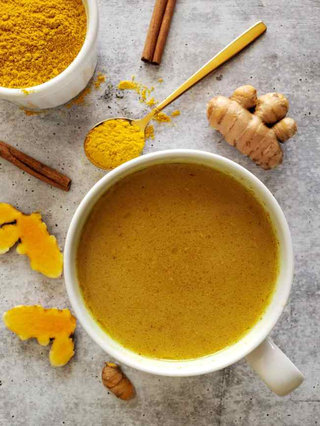 A white ceramic mug is shown full of freshly made golden milk, it is a deep orange to dark yellow in color. Cinnamon sticks, fresh turmeric and a spoonful of turmeric powder are scattered around the perimeter of the mug.