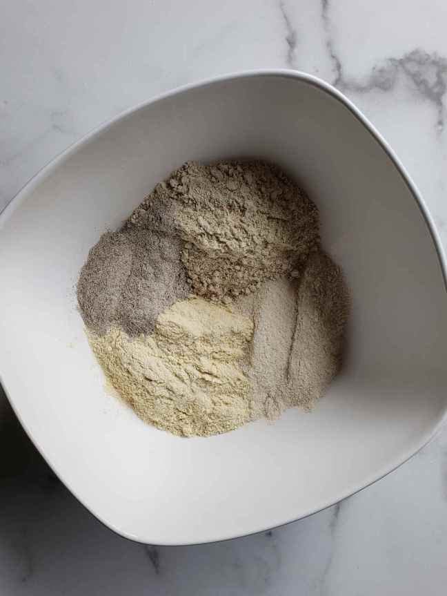 Four types of gluten-free flour and psyllium husk have been added to a square ceramic mixing bowl. Each ingredient is taking up its own portion of the bowl and each one is visibly different from the next.