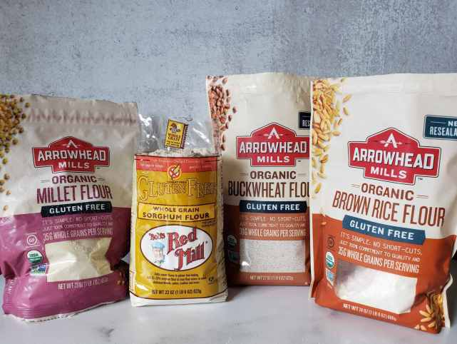 Four bags of gluten-free flour are arranged in a line, from left to right they are: Arrowhead mills Organic Millet Flour, Bob's Red Mill Whole Grain Sorghum Flour, Arrowhead Mills Organic Buckwheat Flour, and Arrowhead Mills Organic Brown Rice Flour.