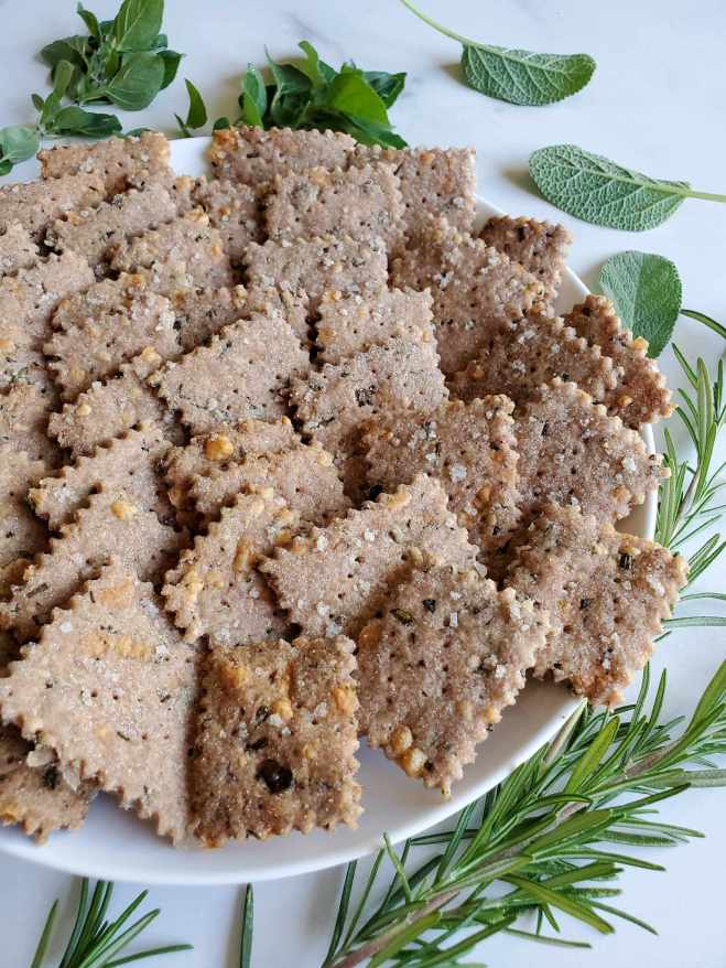 A plate of gluten-free sourdough crackers sitting amongst fresh sage, oregano, thyme, and rosemary that has been scattered around the outside of the plate.