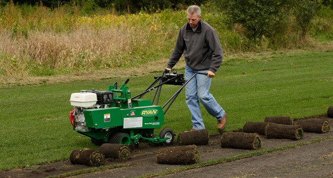 A man is using a sod cutter to remove grass from an area. It rolls the sections of grass into tight cylindrical rolls.