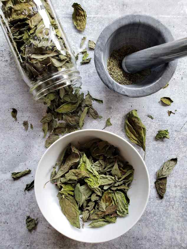 An image consisting of a white ceramic bowl full of dried basil leaves, a quart Mason jar on its side with dried basil leaves spilling out if it, and a mortar and pastel with crushed dried basil sitting in the bottom of the mortar.