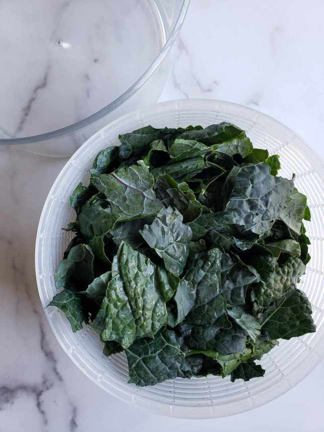 A strainer portion of a salad spinner is featured full of chip sized pieces of fresh lacinato or dino kale.