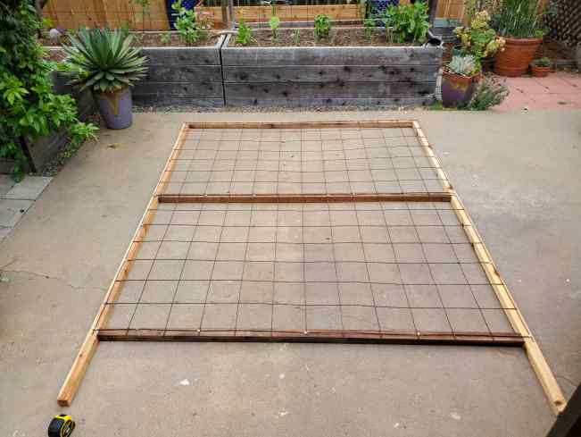 A 8 foot tall, 6 foot wide wood frame metal wire remesh homemade trellis laying on a patio, waiting to be installed.