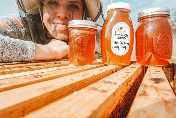 A woman is shown in her bee veil leaning against an open bee box. There are three various sized bottles of honey sitting atop the boxes next to her. Support your local beekeeper by purchasing local honey which can help save pollinators.