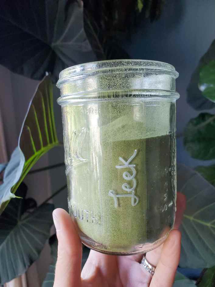 """DeannaCat holding a pint mason jar that is two thirds full of green leek powder. It is piled up in the center of a jar in a slight mound. On the side of the glass jar the word """"leek"""" is written vertically from bottom to top in white marker. In the background are various leaves of indoor houseplants such as alocasia and fiddle leaf fig."""