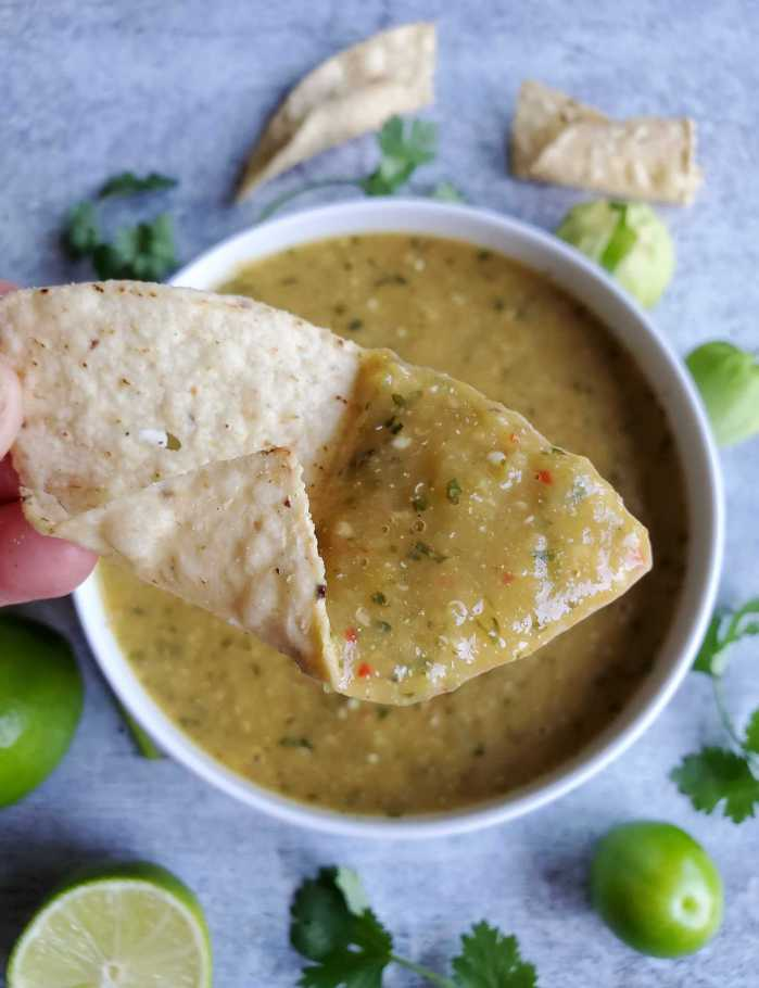 A close up image of a tortilla chip with one third of it covered in green salsa. It is poised over a bowl of roasted tomatillo salsa verde. There are specks of red and green from the chili and cilantro mixed into the slight olive colored salsa. Limes, fresh tomatillos, and sprigs of cilantro are scattered around the outside of the bowl.