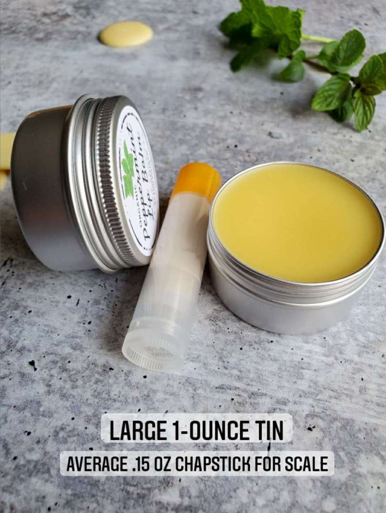 """Two one ounce lip balm tins are shown next to a regular chapstick tube which only contains .15 oz. On the bottom of the image there is a caption with """"Large 1-ounce tin"""" on the top and """"Average .15 oz. chapstick for scale""""."""