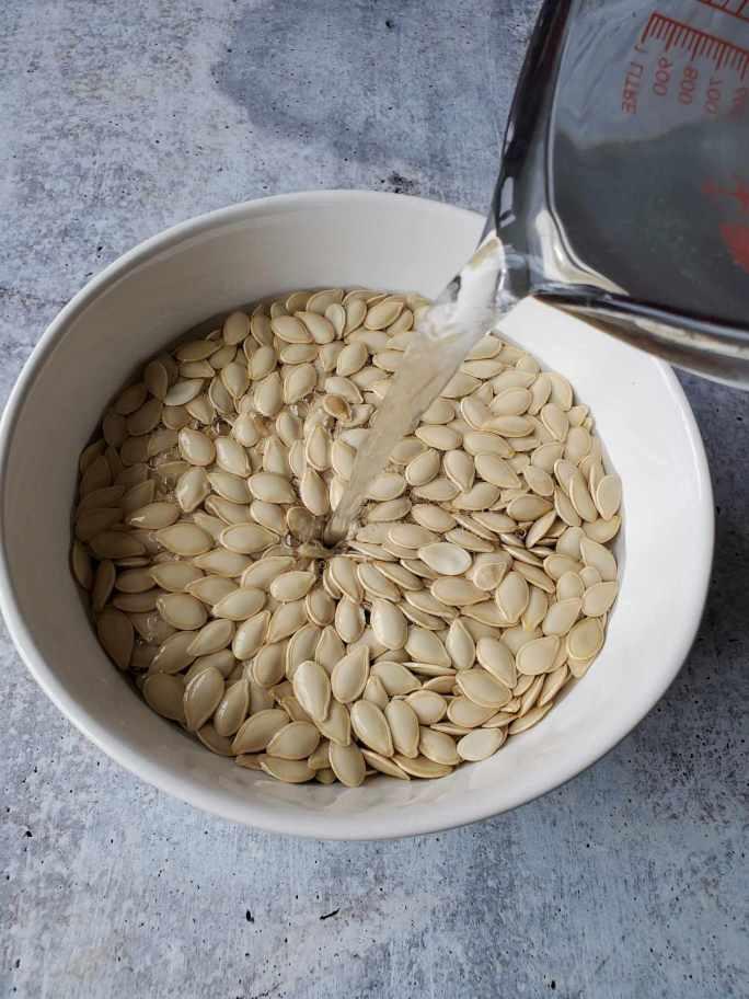Белая керамическая миска наполнена сырыми тыквенными семечками. Стеклянный мерный стаканчик наливает рассол с соленой водой в чашу в правом верхнем углу изображения. Замачивание жареных тыквенных семечек на 6-24 часа - важный шаг в приготовлении лучших жареных тыквенных семечек.