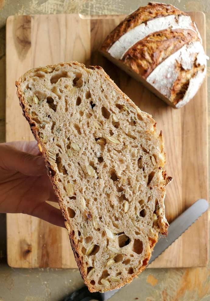 A fresh loaf of sourdough bread is shown. DeannaCat is holding half of the loaf after she sliced it down the middle. The inside of the bread is slightly brown with pumpkin seeds visible throughout the bread. Below is a cutting board with a bread knife and the remaining loaf of bread. Make sourdough healthier by adding nutrient rich additions such as seeds, nuts, and fresh herbs.