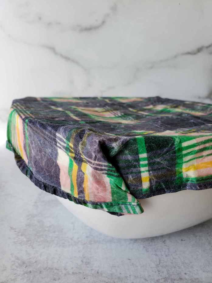 A white ceramic bowl is covered with a homemade beeswax wrap made from a blue, pink, and green patterned shirt. A dough ball of proofing sourdough lies within.
