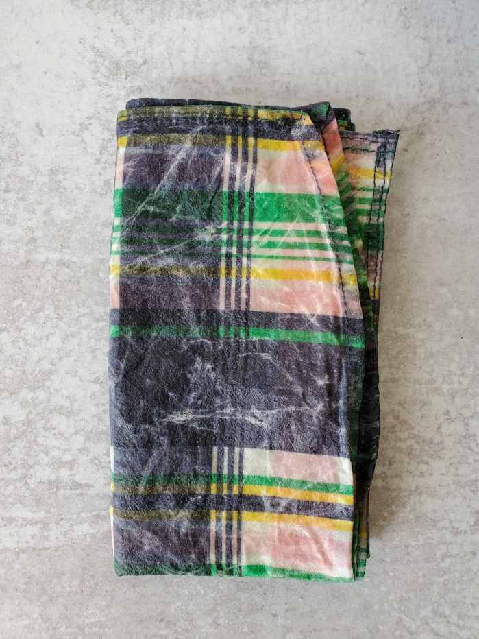 A homemade beeswax wrap made out of a a blue and pink plaid shirt is folded up into a rectangle. It illustrates some white creasing that is caused by the beeswax.