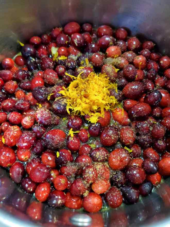 A close up of all the ingredients for fresh homemade cranberry sauce inside a sauce pan, before they started cooking, including whole cranberries, spices sprinkled on top, and a dollop of grated orange peel zest in the middle.