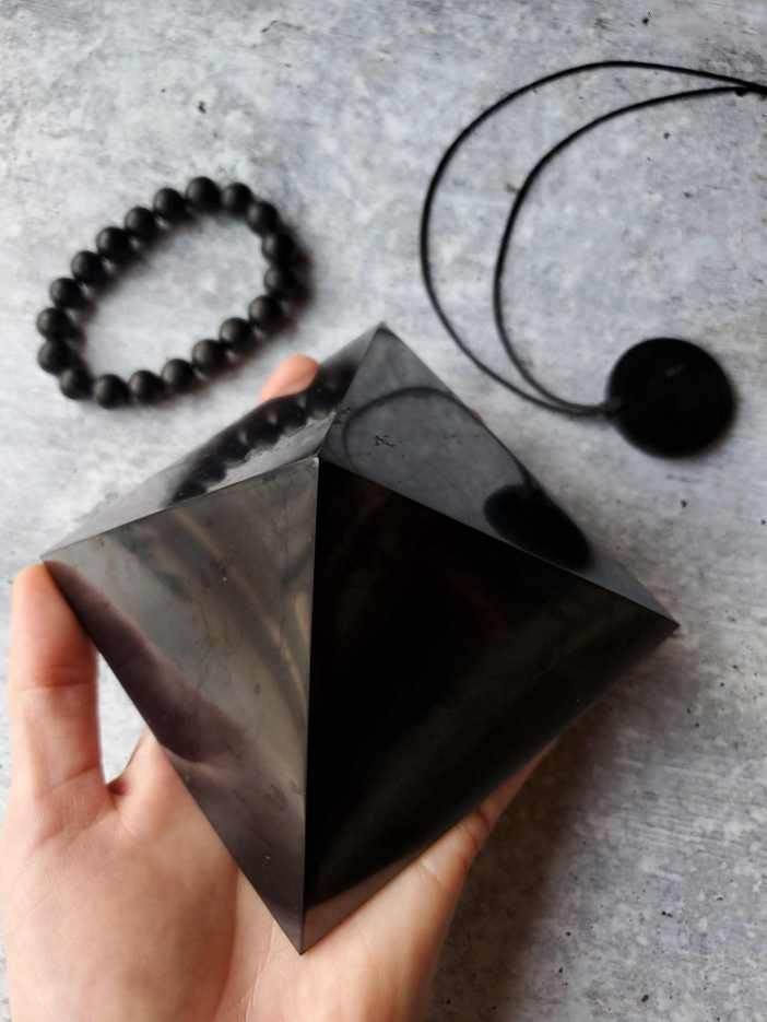 DeannaCat is holding a piece of shungite in the shape of a pyramid. Nearby there is also a shungite bead bracelet as well as a shungite pendent. Shungite, a mineralite, is onyx black in color.
