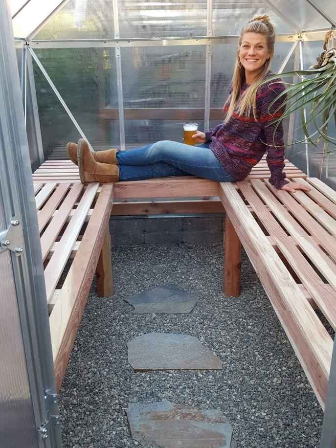 DeannaCat is sitting on her newly made greenhouse benches while she is holding a frosty cold glass of beer. There is a tilandsia hanging on the inside of the greenhouse to the right of the image. Build a greenhouse bench so you can start seedlings and grow various other plants.