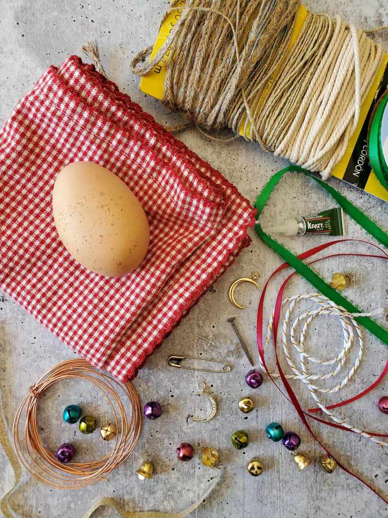 All of the supplies needed to create a blown egg ornament are visible. There is a brown egg, twine of various brown shades, red, green, and white ribbon, copper twine, gold, purple, blue, and green bells, super glue, nail, thumb tack, and safety pin.
