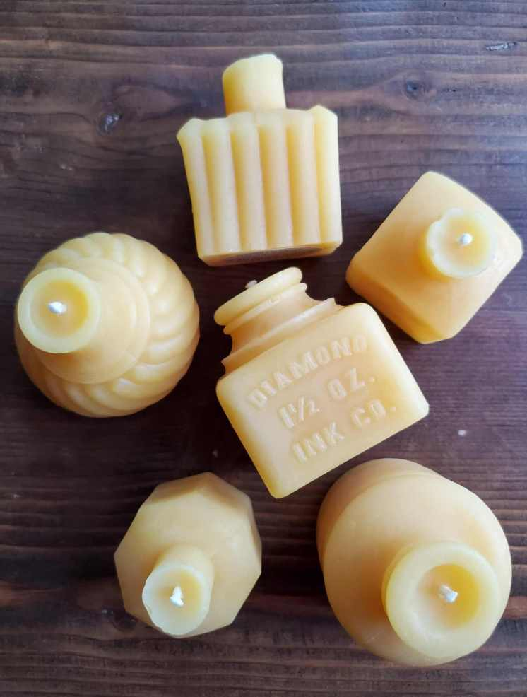 Six beeswax candles of varying shapes and dimensions sit atop a dark walnut backdrop. The candles are a milky yellow color with white wicks. Don't burn toxic candles when one can procure beeswax candles.