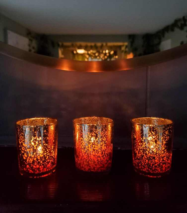 Three votives candle holders with beeswax candles within are lit. The surrounding area is somewhat dark and a portion of a mirror is visible above the candles showing the rest of the room behind. There are holiday lights strung along an entryway amongst a string of garland. Beeswax candles are natural and some of the safest to burn, avoid toxic chemicals with paraffin wax.
