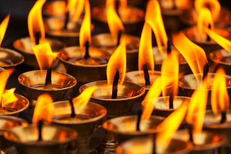 Many copper votive candle holders with black and burning wicks are shown. The holders seem to be filled with an oil that is responsible for the candles staying lit.
