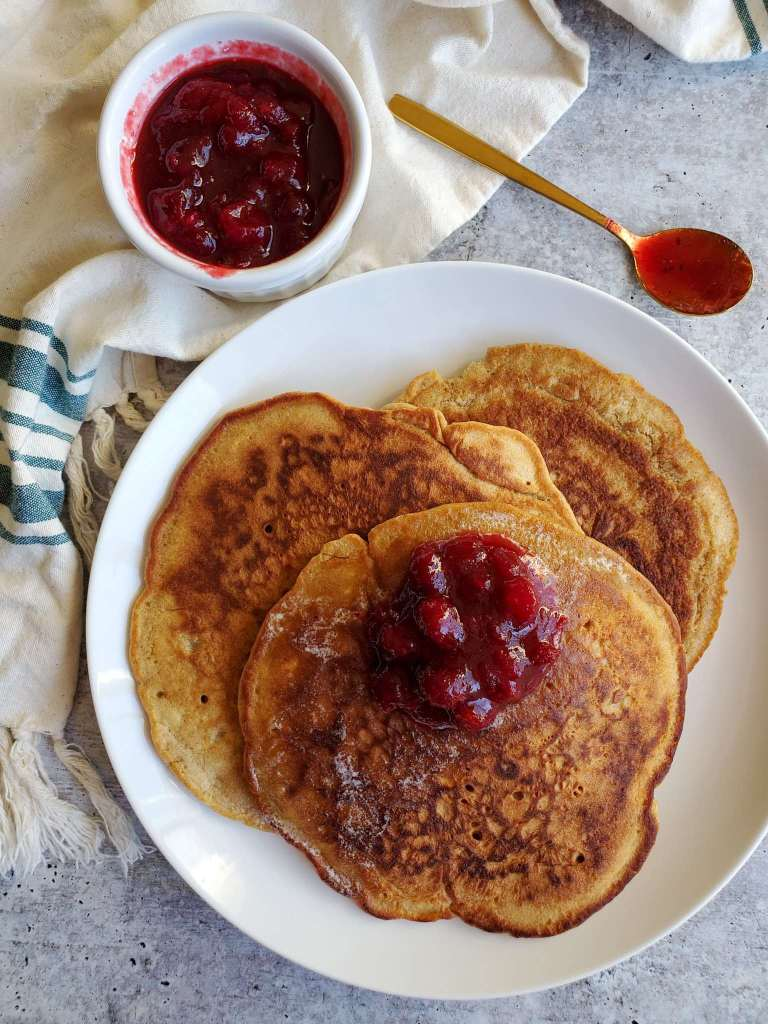 A stack of pancakes sit atop a white ceramic plate. A dollop of cranberry sauce sits on the top pancake.  A ramekin of fresh cranberry sauce sits in the background next to a gold spoon that is now red from the sauce.