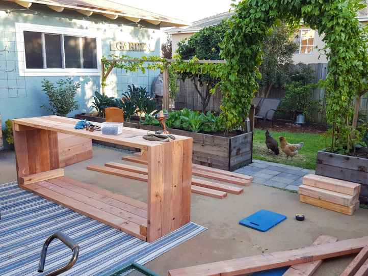 The back patio contains a newly constructed raised garden bed on its side with various pieces and lengths of wood scattered about that are to be used for another bed. There is a drill, gloves, and a box of screws sitting atop the completed raised bed while two chickens look inside into the patio through the arch pathway.