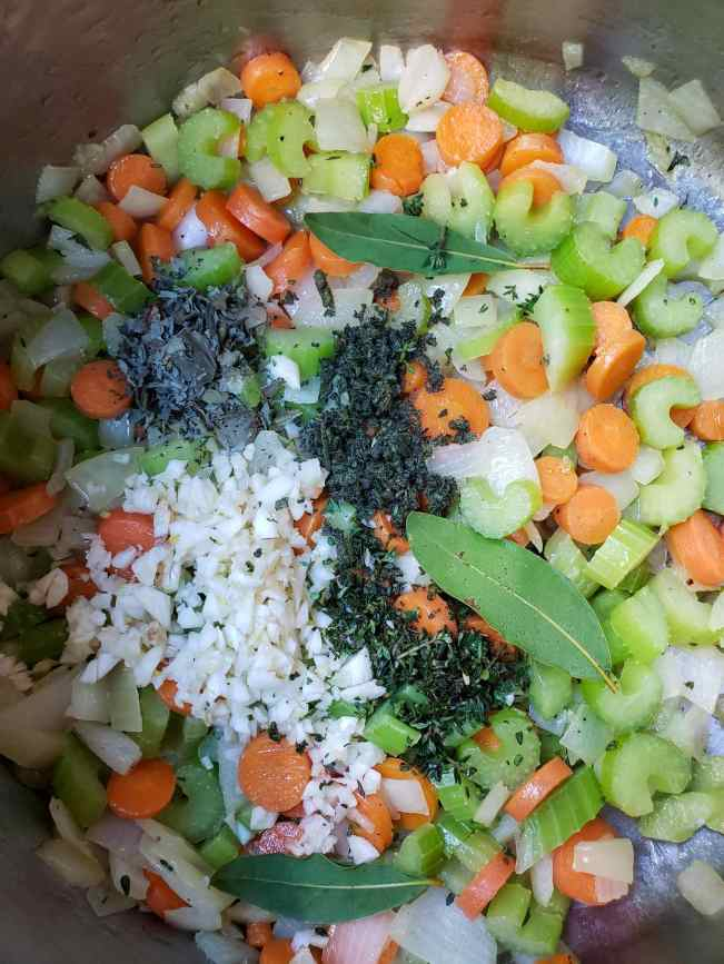 The inside of a stock pot with cooking onion, celery, carrots. Chopped garlic, chopped herbs, dried basil, and three bay leaves sit atop the cooking veggies.