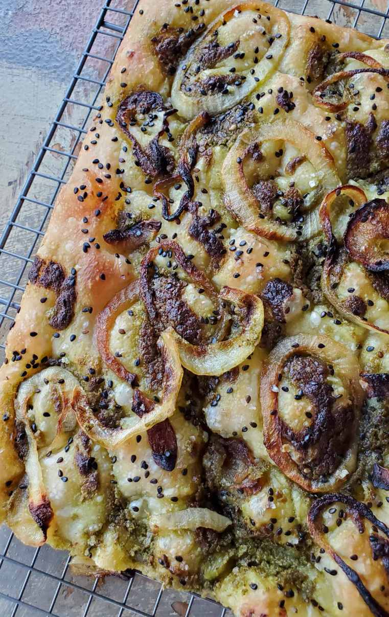 The top of a fresh baked loaf of sourdough is featured with caramelized onions, pockets of dark green pesto, and dotted with sesame seeds. The loaf is bubbly and dark golden brown in color against the sourdough add-ins.