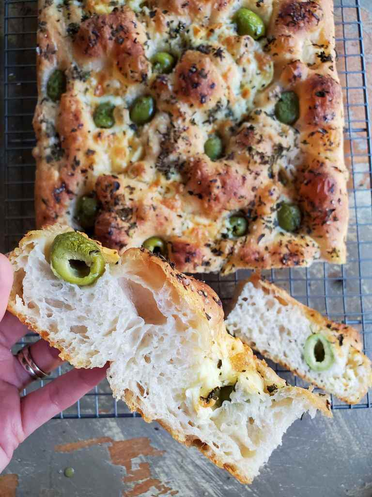 A slice of focaccia is featured, its fluffy interior is visible with air pockets here and there. A green olive is slightly blistered and shrunken from its original size due to the baking process. A pocket of cheese is on the opposite end of the slice. Below lies the remainder of the loaf of focaccia bread on a wire cooling rack. The top of the loaf is dotted with green olives, pockets of cheese, and fresh chopped herbs. Its bubbly surface is golden brown.