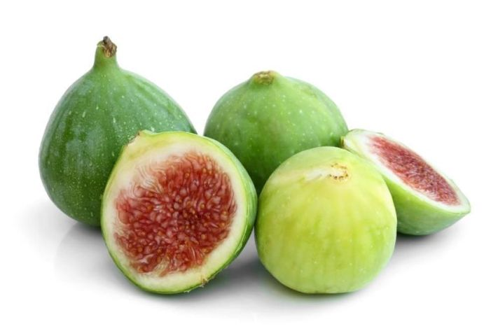 Four green figs sit next to each other in a slight jumble, some of them are more green in color while the riper fig is more yellowish green. One has been cut in half to show its amber flesh.