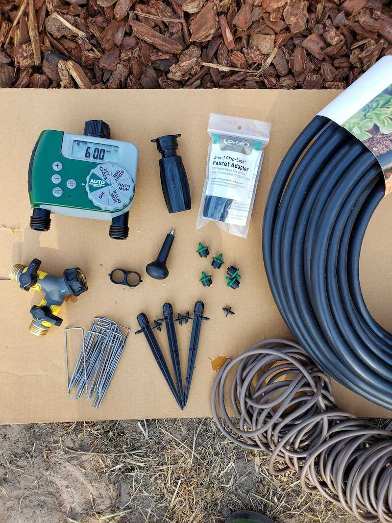 Items you may need for drip irrigation hose bibb setups. There is a piece of cardboard as a back drop with a automated hose timer, faucet adapter, hole punch, emitters, figure eight clamp, y-valve, staples, micro sprinklers, 1/4 inch drip tubing, 1/2 inch tubing, and barbed connectors.
